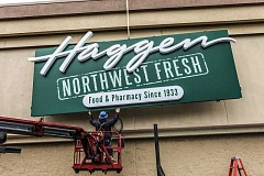 Photo Credit: SUBMITTED PHOTO - A Haggen employee hangs a sign at a newly converted store in Washington. The Albertsons store on Boones Ferry Road in Lake Oswego will be converted in March, the company says.