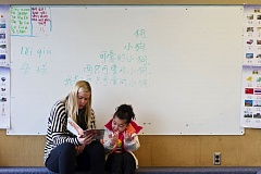 Photo Credit: TRIBUNE PHOTO: JAIME VALDEZ - Grace Cappleman, a graduate of Concordia University and a teacher assistant at Faubion PK-8 School, listens to student Keller Tolen read a book. The partnership between Concordia and Faubion has created a student-instructor ratio of 5-to-1.