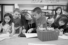 FILE PHOTO: TROY WAYRYNEN - Kindergarten teacher Kammy Breyer, center, helps student Damian Pablo AVendano with a writing assignment at Highland Grade School in Gresham. Also pictured, from left ot right, are students Leonna Maghiari, Cody Laski, Carina Moua and Jaelyn Luna-Garcia.