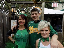 GAZETTE PHOT/RAY PITZ - Allen Bower, owner of Clancy's Pub and Restaurant, poses with waitresses Kayla Seits, left, and Krisanne Driscoll on St. Patrick's Day, the pub's busiest day of the year.