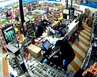 SUBMITTED PHOTO - A masked robber brandishes a gun while robbing an employee of Plaid Pantry near Nike early Friday.