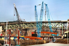 DAVID F. ASHTON - A pair of cranes lift a new Sellwood Bridge steel segment, weighing in at 150 tons, from a barge on the Willamette River.