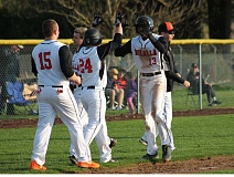 JIM BESEDA/MOLALLA PIONEER - Josey Swain (24) and Keaton Franco (15) greet Reed Aylett (13), whose RBI-triple scored Swain from first base with one out in the eighth inning to lift Molalla to a 4-3 home win over Philomath Thursday.
