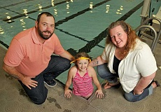 PAMPLIN MEDIA GROUP PHOTO: VERN UYETAKE - Maddie Holly, pictured with parents Brad and Samantha Holly, is wearing an iSwimband. The Hollys have launched Swim Safe Swim Aware, a local program to keep kids safer during pool parties and other gatherings in and around water.