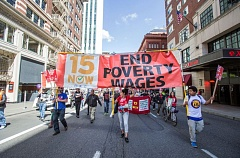 TRIBUNE PHOTO: JONATHAN HOUSE - Protestors march down Broadway Ave. during the afternoon lunch hour to advocate for a $15/hour minimum wage.