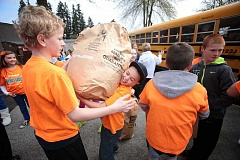 TIMES PHOTO: JONATHAN HOUSE - Students at Mary Woodward Elementary School load bags of clothes onto a school bus during last years Stuff the Bus clothing drive. The drive collects thousands of shirts, pants shoes and other items for needy students in the district