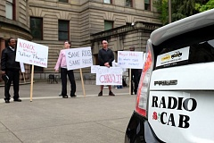 TRIBUNE PHOTO: JAIME VALDEZ - A Prius Radio Cab is parked in front of City Hall as supporters for Portland's cab companies demonstrate against Uber.