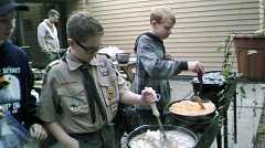 COURTESY OF REMA ROLL - Older scout Logan Kleditz instructs younger Scouts Tim Ohman and Ian Kleditz on Dutch oven cooking. Scoutmaster Jeff Kelso in background supervising activities.