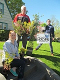 PHOTO BY DICK TRTEK - From left, Megan Dorwin, resource development coordinator for NHA, Warn Industries employee Karl Christensen and Tim Collier, director of communications for NHA, show off some of the plants destined for the Annie Ross House Plant Sale.