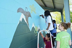 NEWS-TIMES PHOTOS: KATHY FULLER - Cassandra Dunbar oversees students painting on of four new murals on the Echo Shaw Elementary School playground last week. Dunbar works at Echo Shaw through Partnerships for Student Achievement, an AmeriCorps program.
