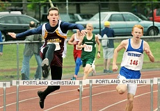 SETH GORDON - Out in front - Austin Friedrich rises over a hurdle during his first-place performance in the 300 hurdles Saturday at the 1A Special District 1 meet at Portland Christian School. Friedrich won in a