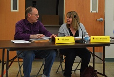 SPOTLIGHT PHOTO: MARK MILLER - Bill Amos (left) and Traci Brumbles (right), candidates for Position 5 on the St. Helens School District's board of directors, chat amicably before a budget committee meeting Tuesday, May 19, about two hours before the first batch of election results were released. According to the unofficial results, Amos defeated Brumbles and two other candidates with nearly half of all voters' support.