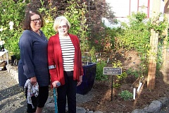 SUBMITTED PHOTO - Members of the Friends of the Rogerson Clematis Garden dedicated a plaque in the honor of Guntis Turks at the Baltic Border of the garden. Linda Beutler, curator of Rogerson Clematis Garden presented the plaque to Leslie Turks. The Turks are longtime members of Rogerson Clematis Garden.