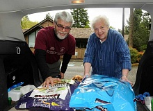 REVIEW PHOTO: VERN UYETAKE - Home food deliveries for pets in Lake Oswego are now a reality, thanks to Ruth Berberich, director of the LOACC Meals on Wheels program. Helping her load up is FIDO Vice President Ron Smith.