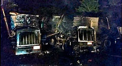 CLACKAMAS FIRE DISTRICT #1 PHOTO  - In the early morning darkness, these are remains of two of the seven trucks that were charred in an overnight million-dollar fire in a trucking contractors parking lot at S.E. 23rd Avenue and Clatsop Street on May 19th.