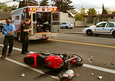 DAVID F. ASHTON - A Portland Police Bureau officer examines the wrecked motorcycle, after the rider who crashed into the rear of a stopped pickup had been loaded into a waiting ambulance.