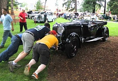NEWS-TIMES FILE PHOTO - Volunteers at the Concours d'Elegance perform a variety of scheduled jobs, from taking tickets to flipping burgers. And sometimes they are called in for unplanned task, like helping position a car with a finicky carburetor.