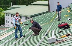 PHOTO COURTESY OF NEIL KELLY REMODELING  - Workers install solar panels in a motel in North Portland's Delta Park area.
