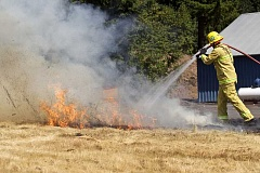 TIMES PHOTO: JAIME VALDEZ - Jon Callahan, a firefighter with Tualatin Valley Fire & Rescue, extinguishes a fire in a grassy field that was ignited by a firework to demonstrate how quickly a fire can spread at the TVF&R Regional Training center in Sherwood.