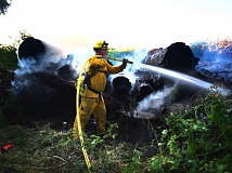 SCAPPOOSE FIRE DISTRICT PHOTO - A Scappoose firefighter fights a blaze started in an abandoned log pile near Crown Zellerbach Road and Miller Road in Scappoose Friday, June 26.