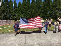 SUBMITTED PHOTO - From left, Tiger Scout Cole Schenk, WEBLOS II Jake Nichols, Star Scout William Hagen, and WEBLOS II Trevor Budiao participate in their troop's flag retirement ceremony on Flag Day in Wilsonville June 14.