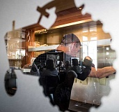NEWS-TIMES PHOTO: CHASE ALLGOOD - As seen through the restaurants tractor logo, a server coordinates with kitchen staff to keep pace with the many customers who packed 1910 Main for one last dinner Saturday.
