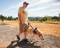 OUTLOOK PHOTO: JOSH KULLA - Terry Blosser walks with his guide dog through Sunrise Park in Troutdale. Blosser, who is legally blind, is working to improve access to local parks for people with disabilities.