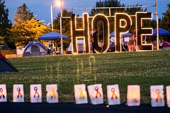 NEWS-TIMES PHOTO: TRAVIS LOOSE - An illuminated Hope sign served as an emotional backdrop to the traditional luminaria ceremony at the Forest Grove Relay for Life Saturday evening, when participants set out glowing tributes to loved ones lost to cancer.