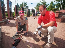 OUTLOOK PHOTO: JOSH KULLA - Boy Scout John Bacon (left) and Hilti North America representative Kevin Stahler place the companys epoxy glue on bricks that will hold brass nameplates at Greshams Heroes Memorial.