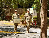 DAVID F. ASHTON - Two members of the 142nd Oregon Air National Guard Explosives Ordnance Disposal Team walk out of the yard carrying the potential military bomb inside a metal container.