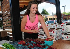 REVIEW PHOTO: VERN UYETAKE - Kate Talbot of Lake Oswego sets out fresh berries, cherries and peppers at the new, 800-square-foot home of Parsons Farms produce stand at Kruse Village.