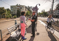 OUTLOOK PHOTO: JOSH KULLA - Gresham Police Officer Dave Anderson talks with a young woman about her request for assistance on a recent morning at the Northeast 172nd Avenue MAX station.