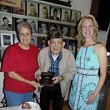 GAZETTE PHOTO: RAY PITZ - Ken Alexander, a World War II veteran, was given a plaque from the Sherwood American Legion Aug. 5, thanking him for his military service. Mayor Krisanna Clark, right, presented Alexander with the award as Alexander's wife Shirley, left, looked on.
