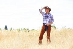 BROADWAY ROSE: CRAIG MITCHELLDYER - Jared Q. Miller - he portrays Curly - gazes into the distance in Broadway Rose Theatre's  production of Oklahoma. It opened Aug. 6 in Tigard.