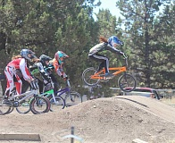 JEFF WILSON/THE PIONEER - Culver's Margie Beeler, out front on the orange bike, clears a jump during the opening seconds of a qualifying race Saturday at the High Desert BMX race track in Bend.