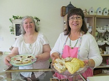 PHOTO BY ELLEN SPITALERI - Beth Moyer, left, owner of the English Garden Tea Cafe, and friend Rowana Holden show off trays of freshly made baked goods offered in the cafe.