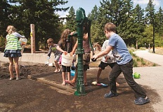OUTLOOK PHOTO: JOSH KULLA - Children play at a water pump and sand pit at the newly renovated Nadaka Nature Park in Gresham.