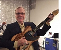 SUBMITTED PHOTO - Paul Allen, owner of the Portland Trail Blazers and Seattle Seahawks who also plays in his own rock band, holds a new guitar just presented to him courtesy of a collaboration between several area high schools that all created it.