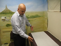 PHOTO BY: RAYMOND RENDLEMAN - Dr. Troy Stoeber prepares an exam room for its next patient. The exam table has white cloth and wheels like an Oregon Trail-era wagon.