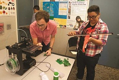 OUTLOOK PHOTO: JOSH KULLA - David Perry of OpenFab PDX demonstrates a 3D printer while Yenni Cazares of Girls Inc!, examines a plastic violin Perry printed himself.