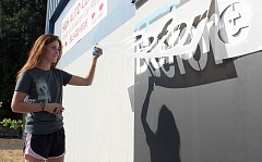 TIMES PHOTO: MILES VANCE - Mallory Matheson of Tigard checks one of the large stencils on the mural shes completing for her National Honor Society project.