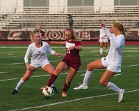 NEWS-TIMES PHOTO: KENT FRASURE - Forest Grove senior Ashton Carow dribbles the ball between two Tualatin defenders during the Vikings' season opener last Thursday. Carow is one of 13 seniors on this year's roster.