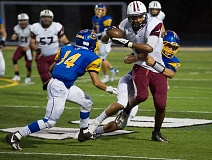 HILLSBORO TRIBUNE PHOTO: KENT FRASURE - Glencoe wide receiver Marquise McKinney gets tackled by Xavier Spencer (14) and Paul Fraizer III (3) on Friday at Aloha. McKinney eventually scored on an 80-yard pass in the fourth quarter to tie up the game, but the Crimson Tide fell to the Warriors 28-21.