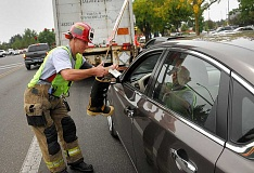 SPOKESMAN PHOTO: VERN UYETAKE - Firefighter Matt Laas helped to collect over $20,000 in donations from motorists in Wilsonville Sept. 15.