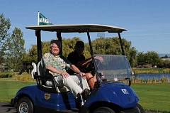 CONTRIBUTED PHOTO - KTVZ weatherman Bob Shaw, left, who served as a grand marshal of the Humane Society event, is seen riding in a golf cart with Meadow Lakes Golf Course Marshal Jim Richards.