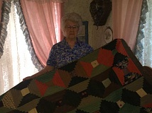 ESTACADA NEWS PHOTO: EMILY LINDSTRAND - Ruth Lazott stands with the quilt her great grandmother made in 1971. The quilt was the oldest one at the Skip-A-Week clubs quilt documentation.