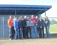 SUSAN MATHENY/MADRAS PIONEER - Rotary member Chris DuPont, center left, receives a plaque from Little League President Robert Holcomb, center right, with board members in the background.