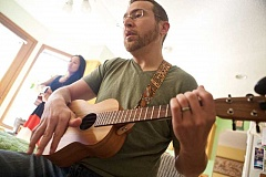 TIMES PHOTO: JAIME VALDEZ - Joshua Waldman and his wife, Lily, in the background, play their ukuleles with a group that they host weekly at their home in Tigard.