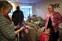 TIMES PHOTO: JAIME VALDEZ - Kathy Armstrong, deputy director of Proud Ground, visits with the Mumba family at their home in Beaverton. Pictured from left; Humphrey, father, Elijah, 7, Jenna, mom, and Lizelle,3.