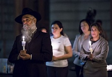 TRIBUNE PHOTO: JONATHAN HOUSE - Rabbi Moshe Wilheim stands with mourners during a candlelight vigil at a Thursday night City Hall for the victims of the Umpqua Community College shootings.